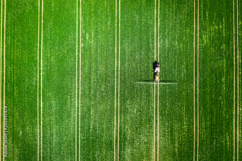Foto auf Leinwand Grun Small tractor spraying the chemicals on the field, aerial view