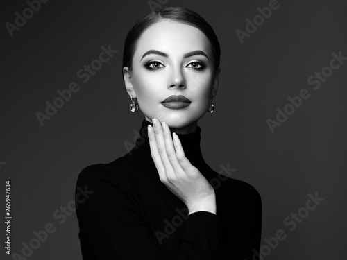 Fotobehang womenART Beautiful Young Woman with Clean Fresh Skin. Perfect Makeup. Beauty Fashion. Plump Lips. Cosmetic Eyeshadow. Smooth Hair. Girl in Black Turtleneck. Black and white photo