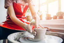 Young Woman In Red Apron Works Behind Potter Wheel With Length, Making Handmade Plate. Concept Of Concentration, Creativity Hand