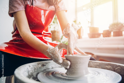 Young woman in red apron works behind potter wheel with length, making handmade plate Wallpaper Mural