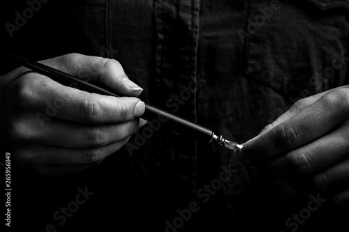 Valokuva  female hand elegantly holding an ink pen with a metal tip close-up on a black background