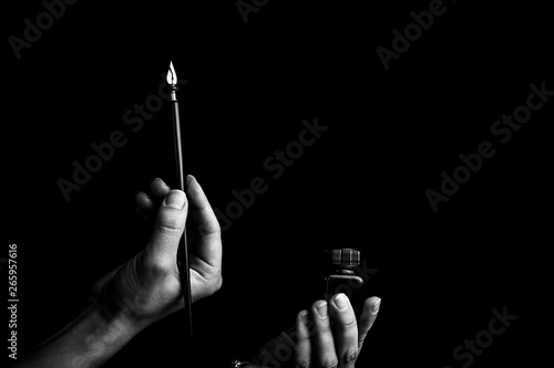 Fotografia, Obraz  female hand elegantly holding an ink pen with a metal tip close-up on a black background