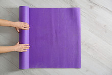 Woman Rolling Yoga Mat On Floor, Top View. Space For Text