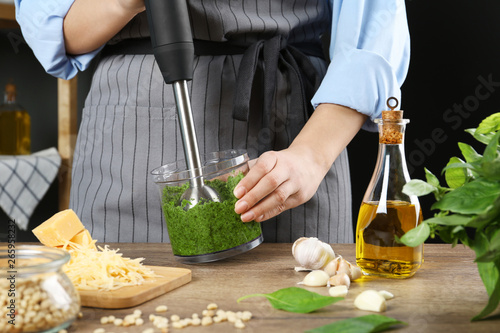 Fotografie, Tablou Woman blending pesto sauce in bowl at table, closeup