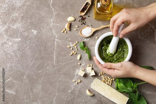 Fotografía Woman mixing pesto sauce with pestle in mortar on grey table, flat lay
