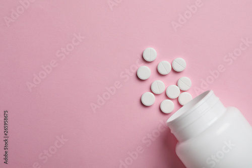 Fotografia  Bottle with pills on color background, flat lay. Space for text