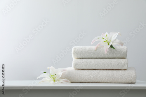 Fototapety, obrazy: Stack of fresh towels with flowers on table against white background. Space for text