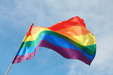 Fototapeta Rainbow - Bright rainbow gay flag fluttering against blue sky. LGBT community