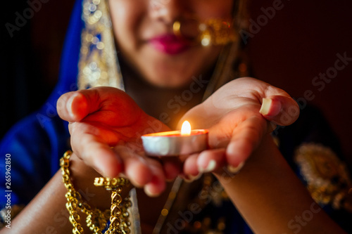 Fototapeta  Woman lighting diyas with nuth nath nose piercing and the golden teak with tradi