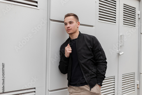 Fotografia Young attractive fashionable man in a vintage stylish jacket in beige pants in a T-shirt relaxes standing near a gray metal wall near the building