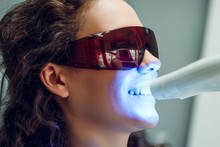 Girl Patient In The Dental Clinic. Teeth Whitening UV Lamp With Photopolymer Composition. Side View.