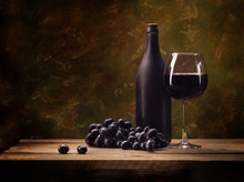 Still Life, Grapes, A Glass Of Wine, A Dark Bottle, On A Motley, Brown Background, On A Wooden Table Top Made Of Natural Old Boards