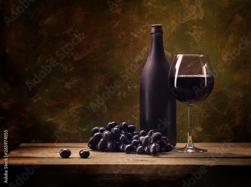 Still life, grapes, a glass of wine, a dark bottle, on a motley, brown backgroun Fototapeta
