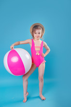 Little Smiling Girl In Swimsuit With Big Inflatable Ball On Blue Background
