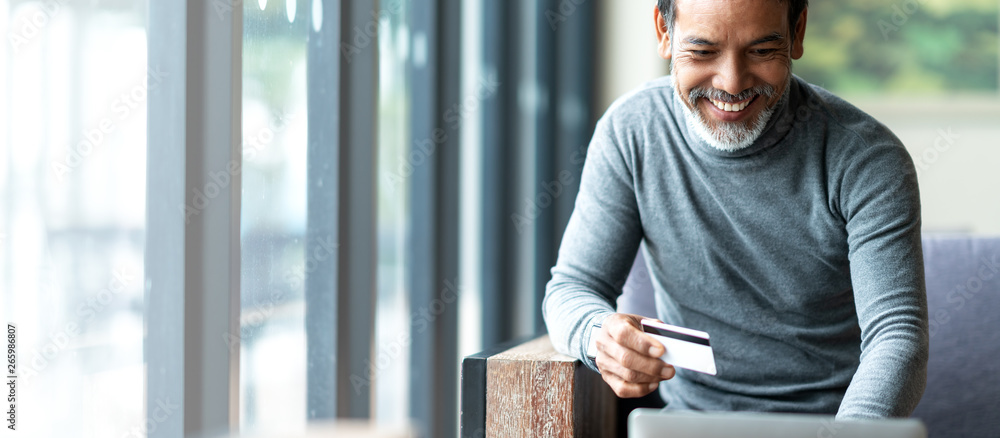 Fototapeta Attractive bearded hipster asian father or Hispanic old man using Laptop and credit card payment shopping online with customer network connection via omni channel system. Older man with technology.