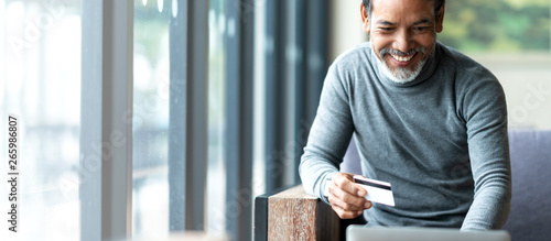 Attractive bearded hipster asian father or Hispanic old man using Laptop and credit card payment shopping online with customer network connection via omni channel system Tableau sur Toile
