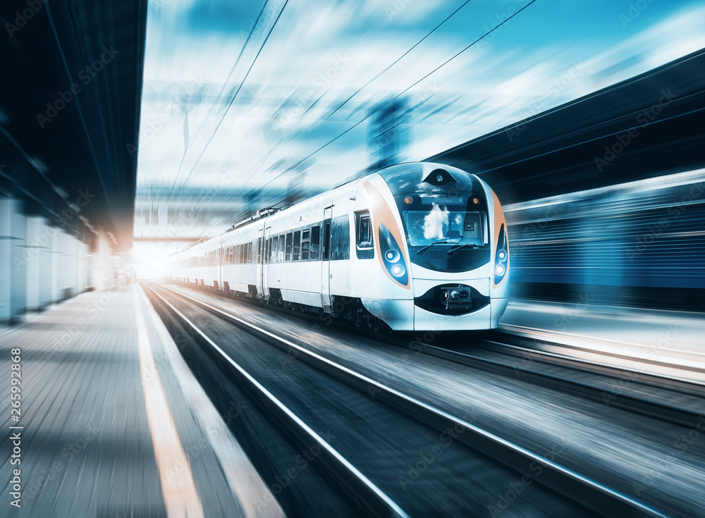 Fototapety, obrazy: High speed train at the railway station at sunset in Europe. Modern intercity train on railway platform. Urban scene with beautiful passenger train on railroad and buildings. Railway landscape