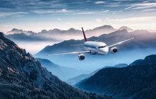 Airplane Is Flying Over Mountains In Fog At Sunset In Summer. Landscape With Passenger Airplane, Hills In Low Clouds, Blue Sky. White Aircraft. Business Travel. Commercial Plane. Aerial View