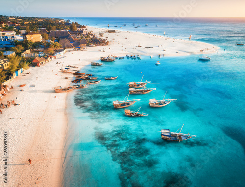 Printed kitchen splashbacks Zanzibar Aerial view of the fishing boats on tropical sea coast with sandy beach at sunset. Summer holiday on Indian Ocean, Zanzibar, Africa. Landscape with boat, buildings, transparent blue water. Top view
