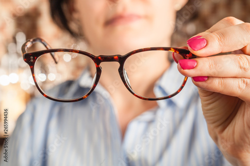 Photo female hand holding a brown framed glasses