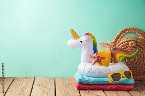 Summer vacation background with orange juice and unicorn pool float on wooden table
