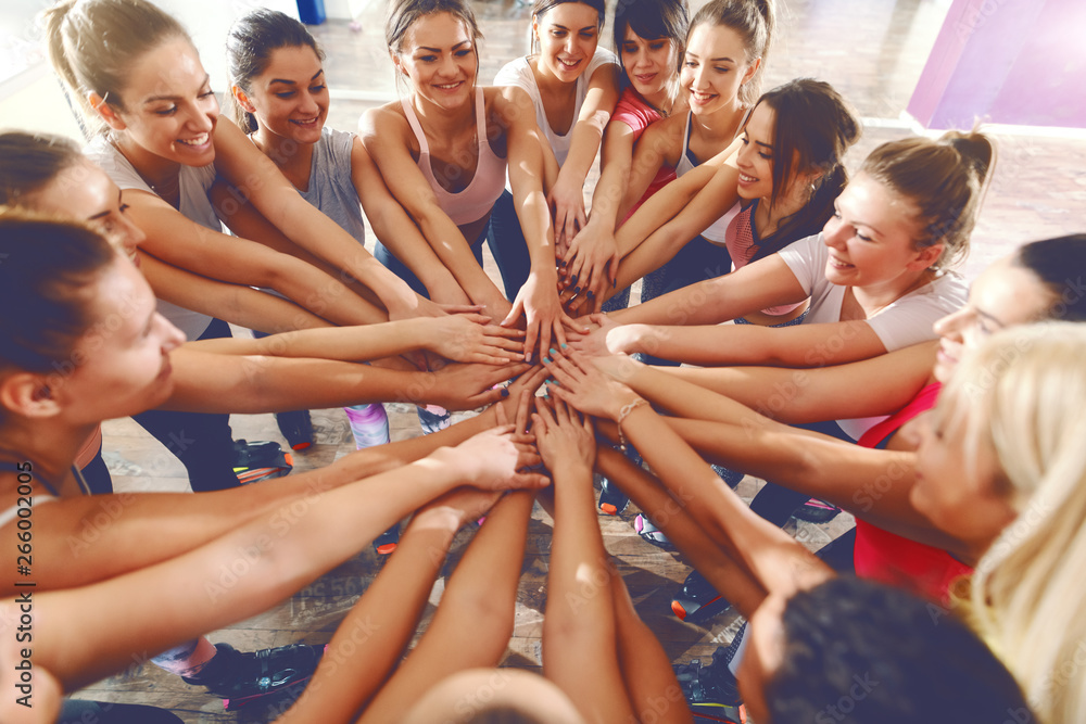 Fototapety, obrazy: Cheerful group of fit women stacking hands in gym. Together we can do anything.
