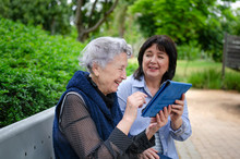 Cheerful Female Carer Shows How To Use The Tablet And A Senior Woman Gladly Repeats