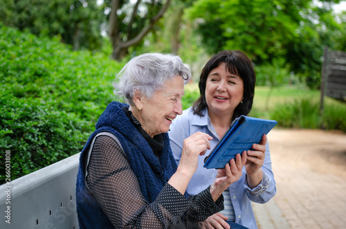 Canvas Print Cheerful female carer shows how to use the tablet and a senior woman gladly repe