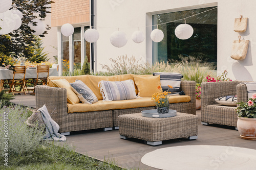 Obraz Real photo of a rattan garden furniture set with lamps and table in the background - fototapety do salonu