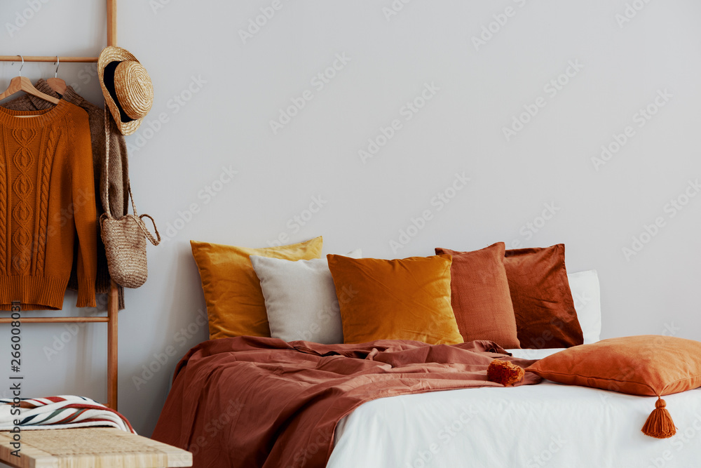 Fototapety, obrazy: Dirty orange pillows on bed in stylish bedroom with copy space on empty wall