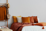 Dirty orange pillows on bed in stylish bedroom with copy space on empty wall