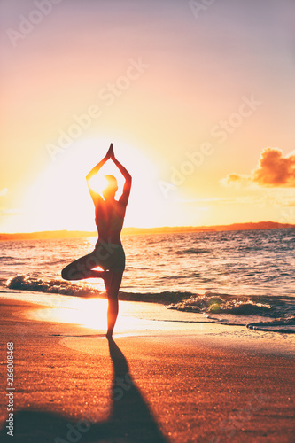 Fototapety, obrazy: Yoga wellness retreat class on morning sunrise beach landscape. Silhouette of girl standing in tree pose meditation vertical background.