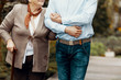 Leinwandbild Motiv Close-up on person supporting smiling senior woman with walking stick