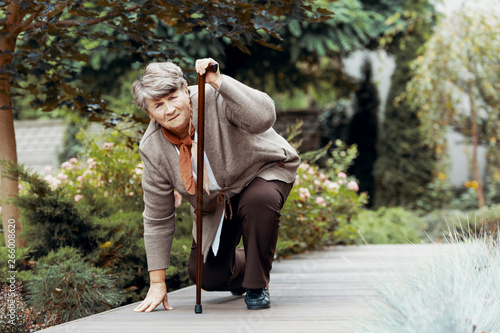 Fototapety, obrazy: Sick senior woman with walking stick waiting for support after chest pain