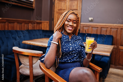 e4d94b17ceb461 Portrait of beautiful young african business woman, wear on blue blouse and  skirt, sitting
