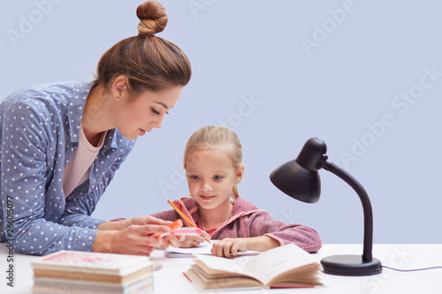 Fotografie, Obraz  Studio shot of little charming girl sits at table, has difficult homework task, her mother trying to help daughter and explains mathematics rules, uses reading lamp for good vision