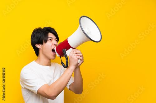 Vászonkép Asian man over isolated yellow wall shouting through a megaphone