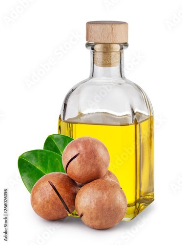 Fototapeta Macadamia oil in bottle with cork and nuts with leaves obraz