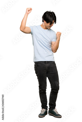 Obraz A full-length shot of a Asian man with blue shirt celebrating a victory over isolated white background - fototapety do salonu