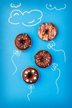 Mini Sweet Donuts With Chocolade Glaze On Blue Background, Creative Food, Donut In A  Shape Of Balloon In The Sky And Painted Clouds. Top View