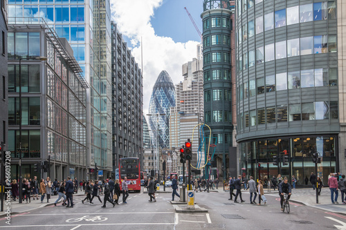 London, UK. City of London busy street with view with lots of people crossing the road, cars and buses