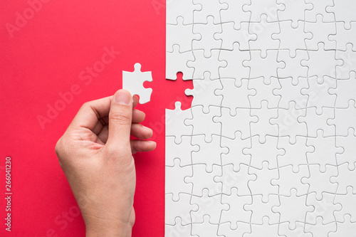 Photo  Hand putting the last piece of white puzzle for business concept or content back