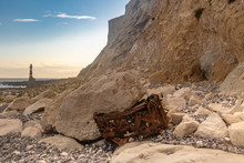 The Rusty Remains Of A Car At The Bottom Of Chalk Cliffs In Sussex, With Beachy Head Lighthouse In The Distance