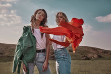 High Fashion Portrait Of Two Stylish Beautiful Woman In Trendy Jackets And Jeans Posing Outdoor. Vogue Style.