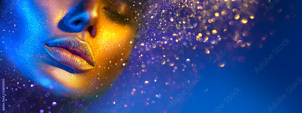 Fototapeta Fashion model woman face in bright sparkles, colorful neon lights, beautiful sexy girl lips. Trendy glowing gold skin make-up. Glitter metallic shine makeup