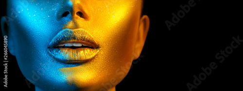 Fashion model woman face in bright sparkles, colorful neon lights, beautiful sexy girl lips. Trendy glowing gold skin make-up. Wide screen