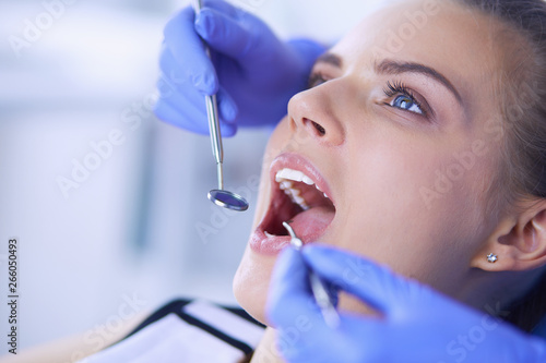 Fototapeta  Young Female patient with open mouth examining dental inspection at dentist office