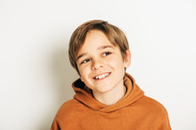 Studio Shot Of Handsome 10 Year Old Boy With Blond Hair, Wearing Brown Hoody, Posing On White Background, Looking Up