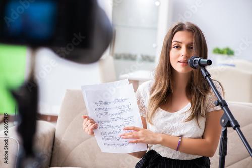 Fotografie, Obraz Female beautiful blogger singing at home
