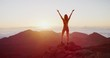 Young athletic woman raising her arms into the air in success pose while she looks out at epic sunrise from a mountaintop, amazing outdoors fitness in slow motion